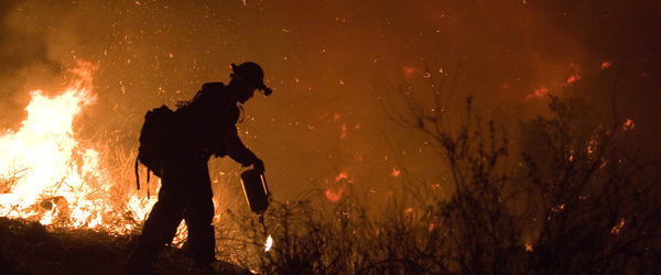 Graphic showing a firefighter walking near flames in a wildfire