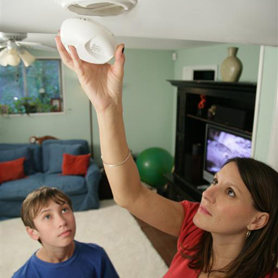 Graphic showing a man demonstrating a Smoke Alarm for two senior citizens