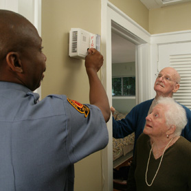 Graphic showing a woman testing a smoke alarm while young man watches