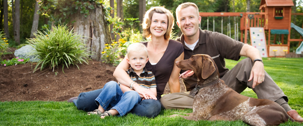 Graphic of a man, woman child and dog sitting on a lawn