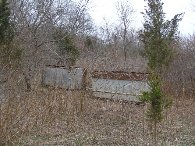 image 36b - 2 large metal bins in a field clearing