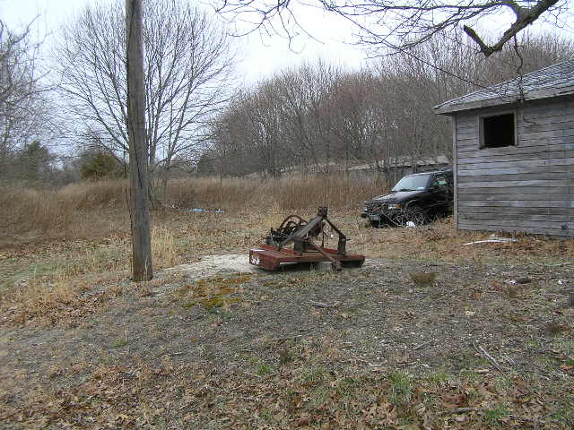 image 47b - old machinery and an abandoned truck sit next to an old abandoned house