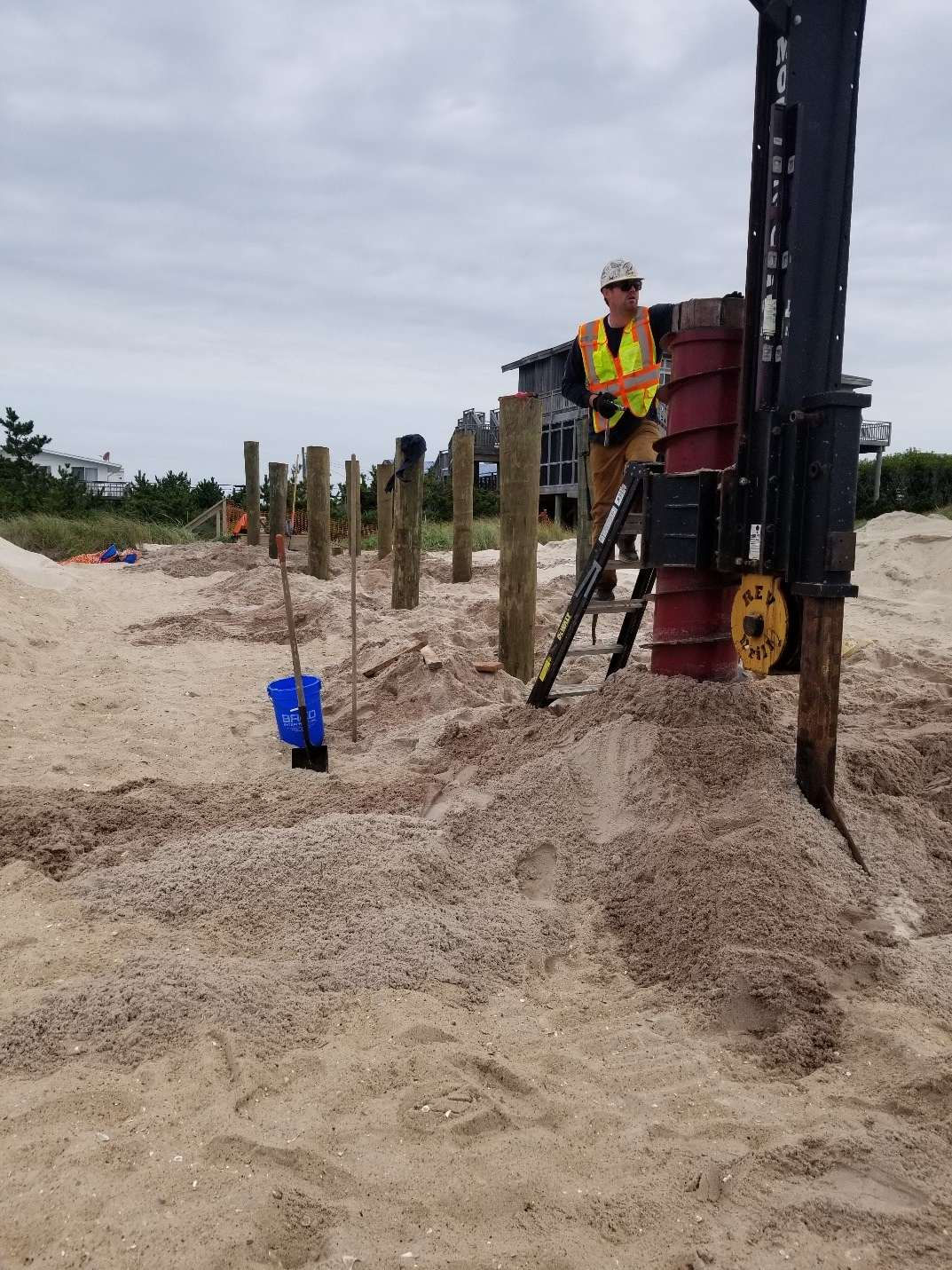 worker adding poles to sand at the davis park shore