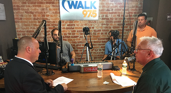 Comptroller Kennedy seated on the right, host and AME President Dan Levler sitting on the left at a table in the live studio of the radio station WALK FM
